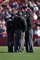 Home plate umpire Anthony Perez (right) meets with the base umpires to discuss a call during the NCAA baseball game between the Holy Cross Crusaders and the South Carolina Gamecocks at Founders Park on February 15, 2020 in Columbia, South Carolina. The Gamecocks defeated the Crusaders 9-4.  (Brian Westerholt/Four Seam Images)