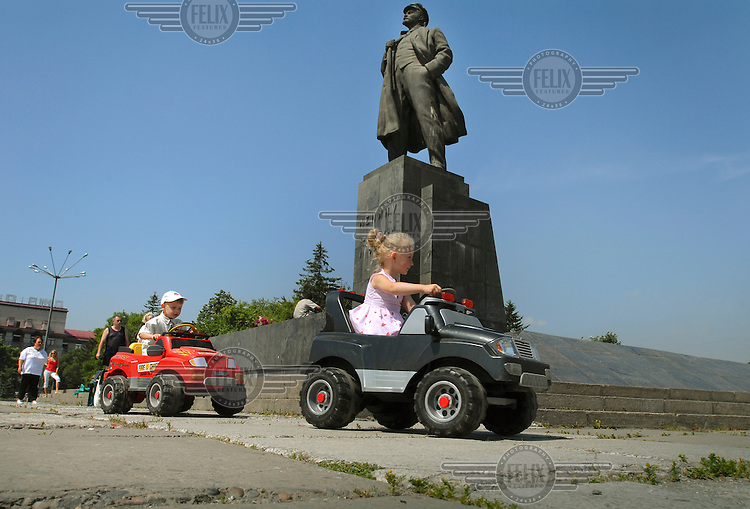 Children drive around in toy cars by a statue of Lenin in the city centre of Krasnoyarsk.