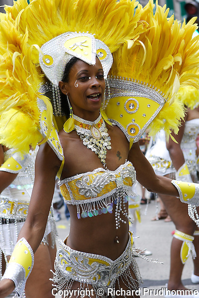a young woman dresses in yellow feathers participates in the Carifiesta parade