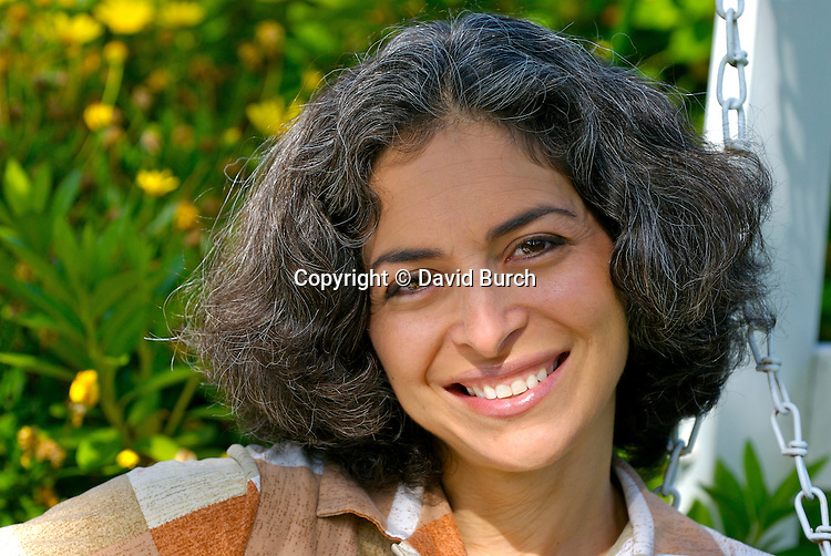 Mature woman sitting on swing smiling