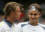 Tennis All England Championships Wimbledon Roger Federer (SUI, r) laechelt Lleyton Hewitt nach seinem 3-Satz-Sieg troestend an.
