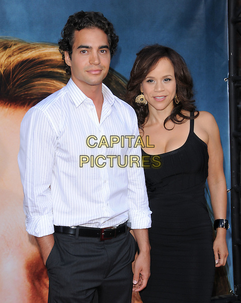 "ROSIE PEREZ & GUEST.The Columbia Pictures' World Premiere of ""Pineapple Express"" held at The Mann's Village Theatre in Westwood, California on .July 31st, 2008 .half length black dress white striped stripes shirt .CAP/DVS.©Debbie VanStory/Capital Pictures."