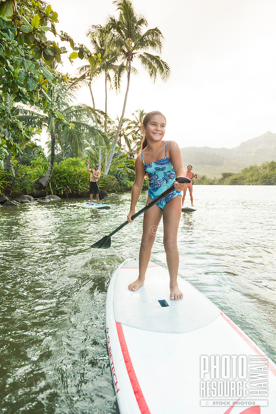 A young girl enjoys learning how to standup paddle with her family on the Wailua River, Kaua'i.