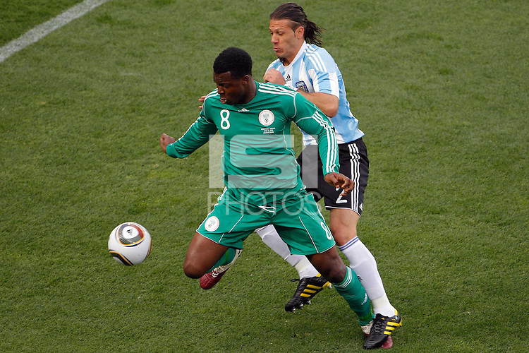 ofJonas Gutierrez (R) of Argentina and Yakubu Aiyegbeni (L) of Nigeria