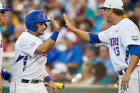 Florida Gators catcher Mike Rivera (4) is greeted by teammate Kirby Snead (13) after scoring against the Miami Hurricanes in the NCAA College World Series on June 13, 2015 at TD Ameritrade Park in Omaha, Nebraska. Florida defeated Miami 15-3. (Andrew Woolley/Four Seam Images)