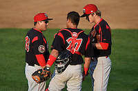 Batavia Muckdogs pitching coach Brendan Sagara (28) talks with catcher catcher Rodrigo Vigil (27) and pitcher pitcher Steven Farnworth (31) during a game against the Tri-City ValleyCats on August 2, 2014 at Joseph L. Bruno Stadium in Troy, New York.  Tri-City defeated Batavia 8-4.  (Mike Janes/Four Seam Images)