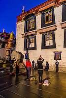 Tibetan pilgrims prostrating themselves in Barkhor Square, outside the Jokhang Temple (the most sacred temple in Tibet), Lhasa, Tibet, China.