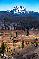 Seen from the east slopes of Cinder Cone, the Painted Dunes were created when volcanic ash fell on hot lava beds and oxidized, giving it reddish hues. In the distance, Lassen Peak, a lava or plug dome volcano, looms.