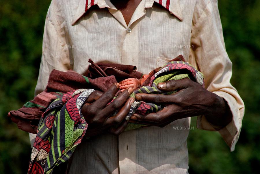 1994. Burundi. Lake Cyohoha. During the Rwandan Genocide, a Burundian Hutu refugee holds his baby in his arms. Burundi. Lac Cyohoha. Pendant le génocide au Rwanda, un réfugié hutu burundais porte son bébé dans ses bras.