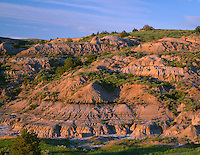 NDTR_102 - USA, North Dakota, Theodore Roosevelt National Park, Evening light defines eroded sedimentary hillside near Boicourt Overlook in the South Unit.