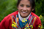 A young Peruvian girl, dressed in traditional clothing, pose for photographs for tourists outside Inca ruins near Cuzco, Peru.