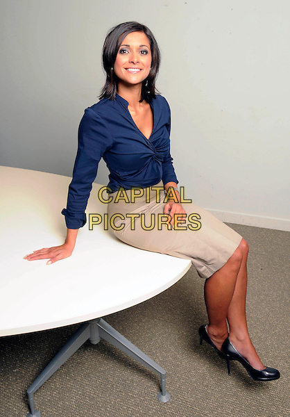 LUCY VERASAMY.Sky Weathergirl Lucy Verasamy pictured at Sky News Centre, London, England, UK, 6th October 2009..full length grey gray skirt blue blouse shirt TV television studio wether forecaster map sitting shoes on table .CAP/FIN.©Steve Finn/Capital Pictures.