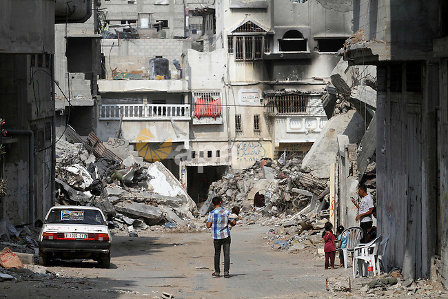 Palestinians children walk next to the destroyed houses and buildings that were destroyed during the devastating 50-day war between Israel and Hamas at Al-Shojae'ya neighborhood east of Gaza City on October 11, 2014. ahead of a donors conference in Cairo aimed at gathering efforts to the reconstruction of the Gaza Strip after the devastating 50-day war between Israel and the Hamas militants who run the coastal Palestinian enclave. The Palestinian government has unveiled a 76-page reconstruction plan for Gaza, calling for $4 billion to rebuild the war-battered territory, with the largest amount going to build housing for some 100,000 left homeless. Photo by Mohammed Asad