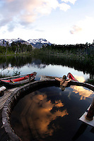 A woman enjoys sunset in hot tub at mountain lake in Patagonia, Chile as clouds are reflected in the water.