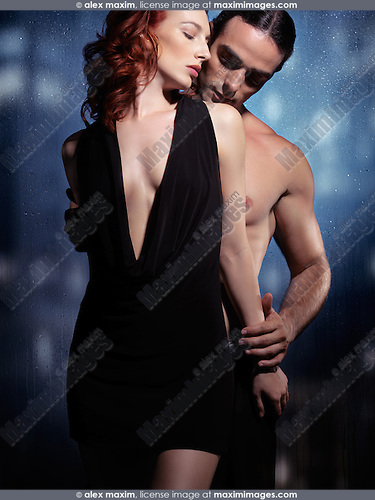 Sexy young couple artistic sensual portrait. Young woman in black dress and young man with bare torso standing in front of a wet window on a rainy night
