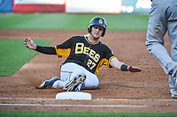 Jett Bandy (27) of the Salt Lake Bees slides back into first base during the game against the Las Vegas 51s in Pacific Coast League action at Smith's Ballpark on June 25, 2015 in Salt Lake City, Utah. Las Vegas defeated Salt Lake 20-8.  (Stephen Smith/Four Seam Images)