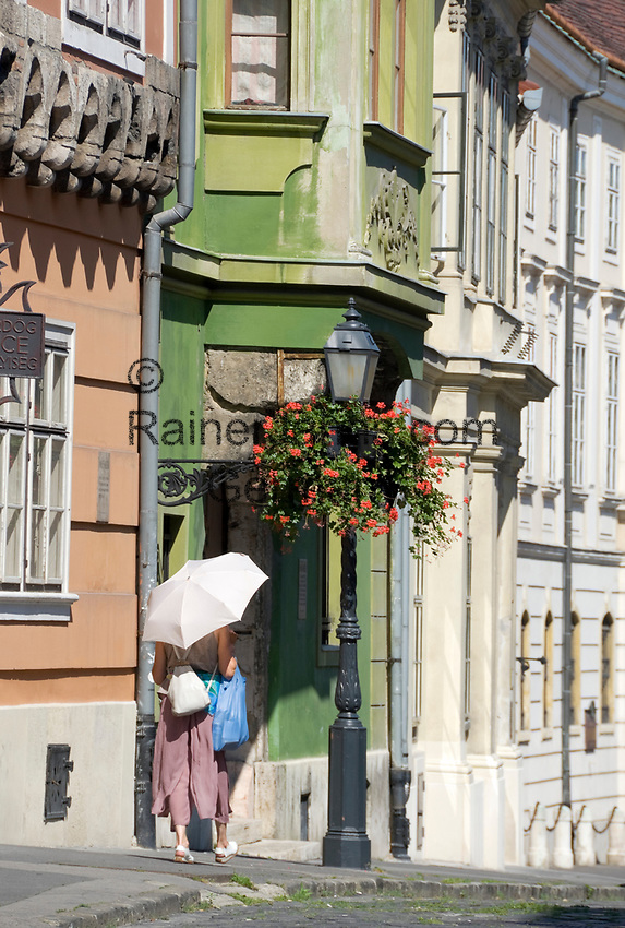 HUN, Ungarn, Budapest, Stadteil Buda, Burgviertel: alte Kaufmannshaeuser in der Parlamentsgasse (Országház utca), Frau mit Regenschirm als Sonnenschutz | HUN, Hungary, Budapest, Castle District: old merchant houses at Parliament lane (Országház utca), woman with umbrella as sun protection