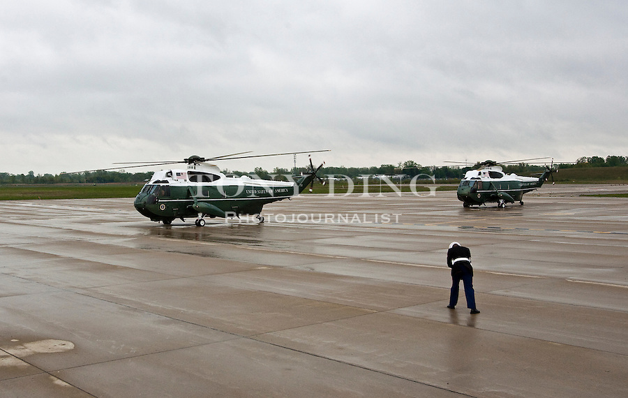 A Marine Corps officer braces himself against the wind generated by Marine One, left, as it prepares to take off with President Barack Obama onboard for Ann Arbor, Mich., at Detroit Metropolitan Airport, Saturday, May 1, 2010, in Romulus, Mich. President Obama is heading to give the commencement address at the University of Michigan's football stadium. (AP Photo/Tony Ding)