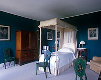 A single four-poster bed draped in crisp white fabric stands out against the dark turquoise colour of the bedroom walls