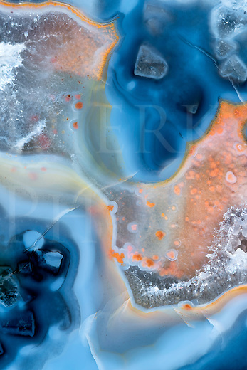 Natural agate crystals showing curves and patterns in blues and orange, close up fine art photography.