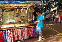 A shopper stands by a stall fronted with artificial leis at the International Market Place in Waikiki.