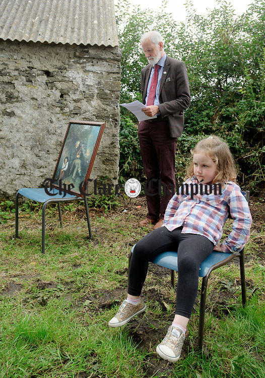 Young Laura Griffin watches proceedings as Frank Whelan, chairman of Fleadh 2017 Ennis waits to speak at the unveiling of a memorial at the house where the blind piper Patrick O Brien was born at Labasheeda. Photograph by John Kelly.