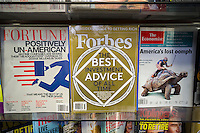 Forbes magazine is seen on a newsstand with other business magazines in New York on Saturday, July 19, 2014. The media company, controlled by the Forbes family, has sold the magazine and the rest of the company to a group of Hong Kong investors led by Integrated Asset Management, a Hong Kong based company. (© Richard B. Levine)