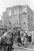 Photo from the NIOD's Huizinga collection. People on the street listen attentively to an English-language news broadcast, which can be heard through a loudspeaker from the window of a private house, at the top right where the flag hangs. Menno Huizinga was part of the Hidden Camera and took pictures illegally during the occupation. He did this mainly in his hometown The Hague.