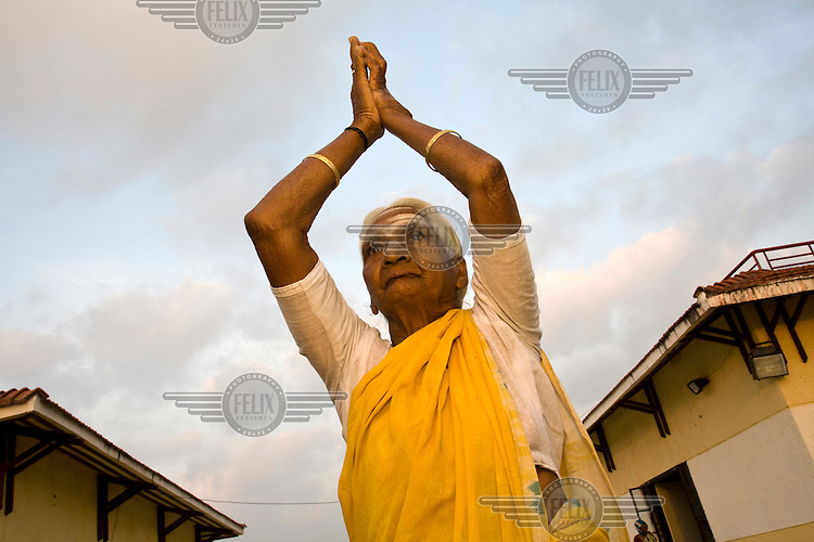 Pattu salutes the sun at dawn at the Tamaraikulum Elders' village. The village is a pioneering experiment initially set up by HelpAge India after the Asian Tsunami to help elderly people displaced by the natural disaster. Today, the village is a self-sustaining community providing a family environment where more able-bodied residents assist the less able-bodied and provides 100 older people with a safe place to live, free healthcare, emotional security, a good diet and professional care and support...