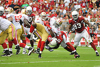 Sept. 13, 2009; Glendale, AZ, USA; San Francisco 49ers running back (21) Frank Gore breaks the tackle from Arizona Cardinals safety Antrel Rolle to score a touchdown in the second quarter at University of Phoenix Stadium. Mandatory Credit: Mark J. Rebilas-