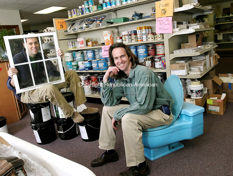 NEW BRITAIN, CT, 28 MARCH 2006- 032806BZ11- Volunteer Bryan Gordon, 37, of Glastonbury, left, holding a window and sitting on a pile of of 5 gallon buckets of carpet adhesive and John Powers, board treasurer, sitting on a used toilet, pose for a picture inside the ReCONNstruction Center on South Street in New Britain. <br /> Jamison C. Bazinet Republican-American