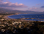 Santa Barbara at sunset with beach and coastline along the Pacific Ocean with Stearns Wharf and Santa Ynez Mountain Range in background Santa Barbara California USA