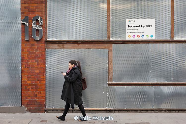 A woman walks past an empty office building in Shoreditch, London, a run-down commercial district  also known as Silicon Roundabout, which is undergoing gentrification as it becomes a centre for web-based companies and IT start-ups.