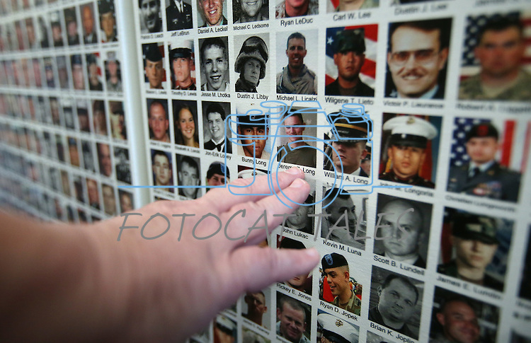 Patsy Cave, of Carson City, locates the photo of her 18-year-old nephew on the Wall of the Dead at the opening ceremony of the Always Lost: A Meditation on War exhibit at the Legislative Building in Carson City, Nev., on Monday, April 6, 2015. Her nephew, Marine Lance Cpl. Jeremy Z. Long, was killed Aug. 10, 2006 in Afghanistan. <br /> Photo by Cathleen Allison/Nevada Photo Source