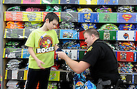 NWA Media/ J. T. WAMPLER- Isaiah Collins, 9, of Springdale gets some shopping assistance from Springdale police oficer Taylor Talley Friday Dec. 12, 2014 during the department's annual Shop with a Cop program. Around fifty officers took children shopping at the Pleasant St. Wal-Mart spending around $33,000. The funds came from donations, corporate spoonsorships and fund raisers.
