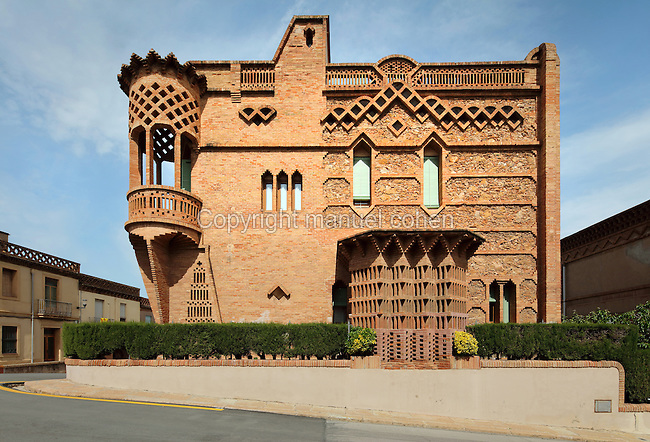 Ca l'Espinal, built 1900 by Joan Rubio, 1870-1952, as the residence of Mr Espinal the factory manager and company administrator, in the Colonia Guell, a workers' colony set up by Eusebi Guell in Santa Coloma de Cervello, Barcelona, Catalonia, Spain. The building has a stone and brick facade with brick lattice work and a medieval style corner turret. The colony was begun in 1890 on Guell's estate Can Soler de la Torre, with a hospital, boardinghouse, schools, shops, theatres, chapel, factories and workers' housing. The Catalan Modernist architect Antoni Gaudi, 1852-1926, was in charge of the project, collaborating with Francesc Berenguer, Joan Rubio and Josep Canaleta. Picture by Manuel Cohen