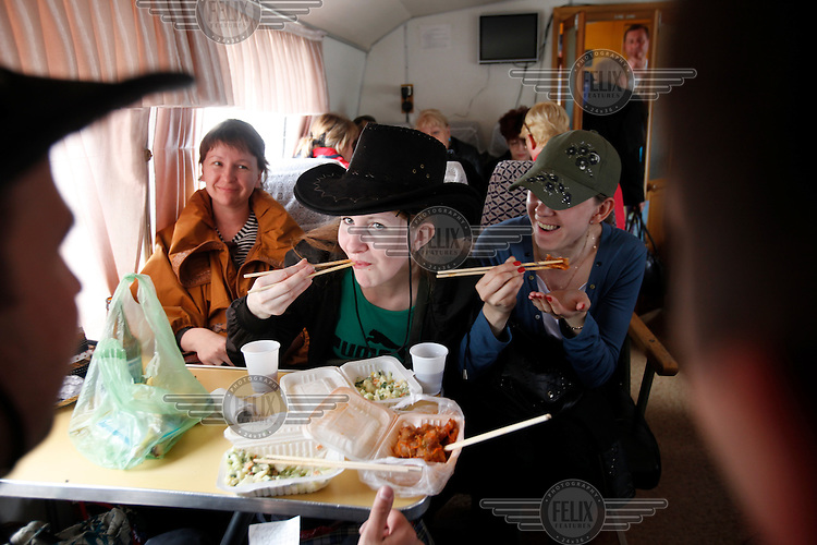 Russian youngsters from Khabarovsk city  enjoy a Chinese meal on the boat on their way home from on a shopping spree in Fuyuan town in China, just across the Amur River that separates Russia and China,. Prices for goods and services are much lower in China.