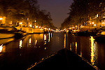 A boat sails through  through the canals at night in Amsterdam, the Netherlands.