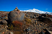 A stone cairn on the lower slopes of Mt Ruapehu, Tukino Peak in the distance, Tongariro National Park, Central Plateau, North Island, New Zealand