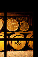 Stored on vast open shelves and kept securely under lock and key behind metal gates, casks of whisky left to mature in a distillery cellar