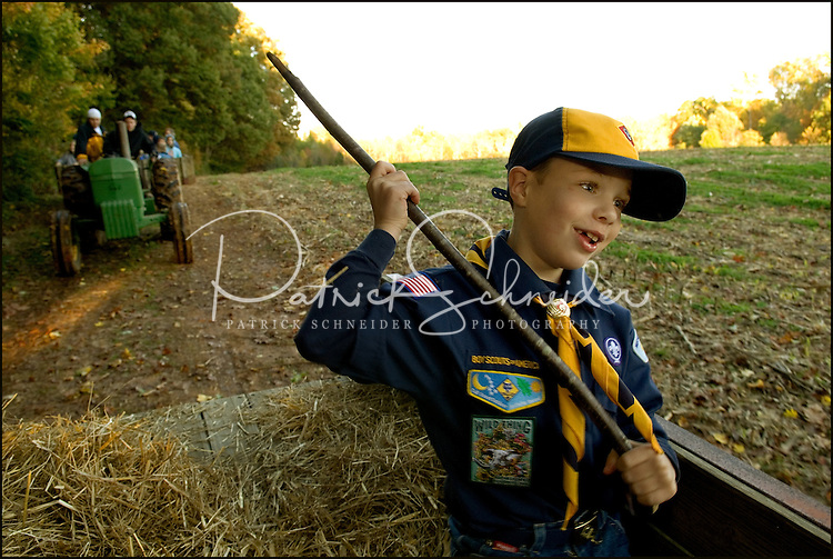 A young boy / cub scout (model released) rides on a hay wagon during a fall outing.