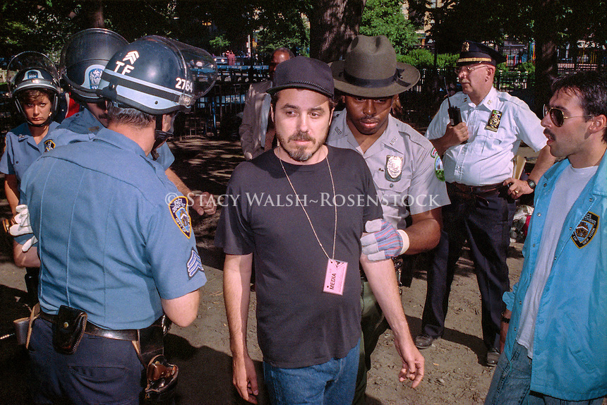 New York, NY - 3 June 1991 - Police escort activist photographer John Penley out of the park as the City evicts squatters from Tompkins Square