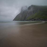 Low misty clouds hide the summit of Ryten over Kvalvika beach, Moskenesøy, Lofoten Islands, Norway