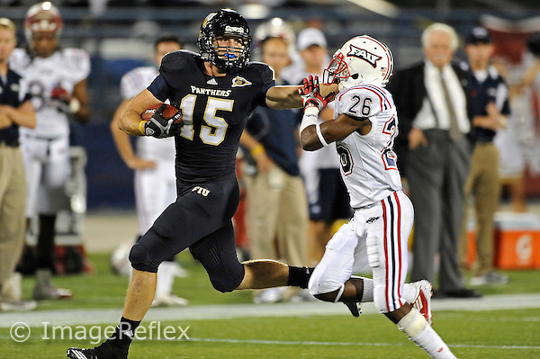 12 November 2011:  FIU tight end Colt Anderson (15) attempts to hold off Florida Atlantic cornerback Curtis Cross (26) while returning a short kickoff 49 yards to the 19 yard line in the third quarter as the FIU Golden Panthers defeated the Florida Atlantic University Owls, 41-7, to win the annual Shula Bowl game, at FIU Stadium in Miami, Florida.