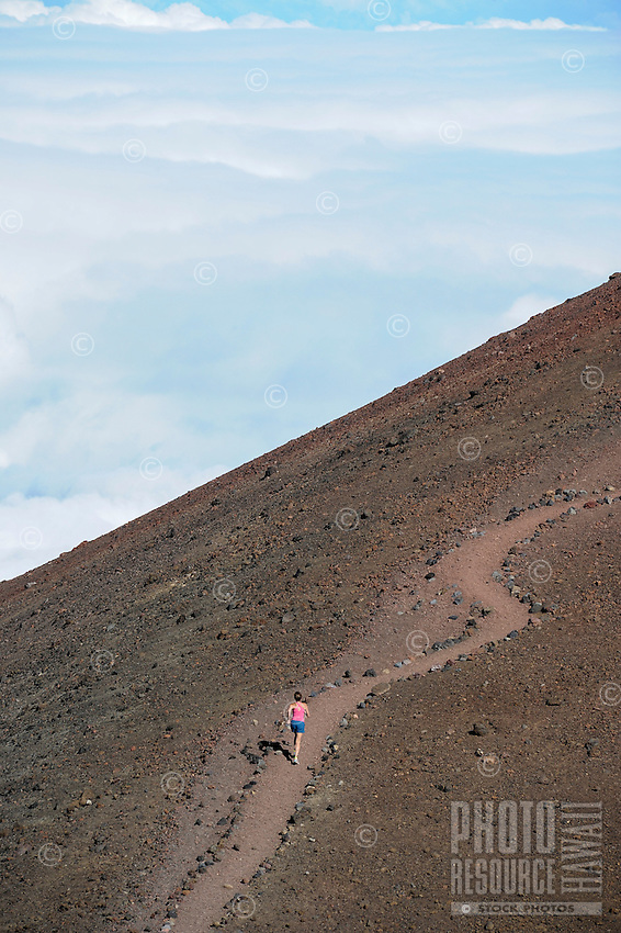 A woman hikes up a trail on Mauna Kea, Big Island of Hawai'i.