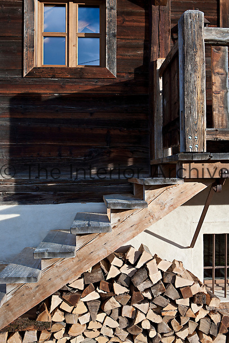 Logs for the chalet's open fires are stacked neatly beneath the wooden steps leading up to the front door