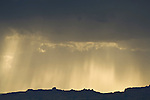 Late afternoon thunderstorm brings moisture to the San Rafael Reef as crepuscular rays of the sun stream through the clouds, Utah.