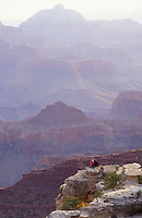 USA, Arizona, Grand Canyon National Park, couple sitting on a ledge at Mathers Point enjoying the view of the canyon