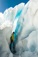 Young woman enjoys turquoise ice feature on Franz Josef Glacier, Westland Tai Poutini National Park, West Coast, UNESCO World Heritage Area, New Zealand, NZ