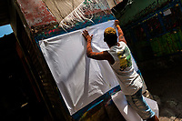 """A Colombian sign painter sticks a blank paper on the wall in the sign painting workshop in Cartagena, Colombia, 15 April 2018. Hidden in the dark, narrow alleys of Bazurto market, a group of dozen young men gathered around José Corredor (""""Runner""""), the master painter, produce every day hundreds of hand-painted posters. Although the vast majority of the production is designed for a cheap visual promotion of popular Champeta music parties, held every weekend around the city, Runner and his apprentices also create other graphic design artworks, based on brush lettering technique. Using simple brushes and bright paints, the artisanal workshop keeps the traditional sign painting art alive."""